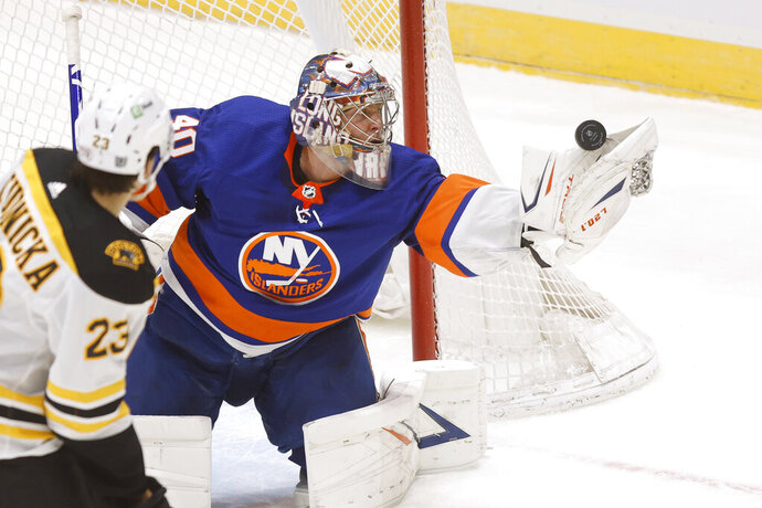 New York Islanders goalie Semyon Varlamov (40), of Russia, makes a glove-save against the Boston Bruins during the second period of an NHL hockey game Monday, Jan. 18, 2021, in Uniondale, N.Y. (AP Photo/Jason DeCrow)