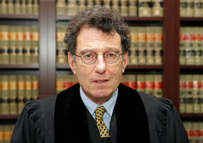 FILE – In this Jan. 11, 2018, file photo, U.S. District Judge Dan Polster poses for a portrait in his office in Cleveland. Polster is holding a hearing Tuesday, June 25, 2019,  in Cleveland on a plan pitched by lawyers for local governments on distributing money to nearly 25,000 municipal and county governments. The plan would take effect if companies that make and distribute the powerful prescription painkillers agree to one or more legal settlements. (AP Photo/Tony Dejak, File)