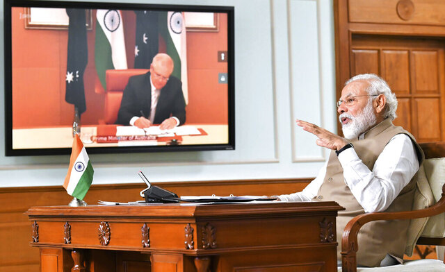In this handout photo provided by the Press Information Bureau, Indian Prime Minister Narendra Modi speaks during a virtual meeting with Australian Prime Minister Scott Morrison, in New Delhi, India, Thursday, June 4, 2020. India and Australia upgraded their relationship with a raft of agreements Thursday, including strengthening defense ties and cooperation in the Indo-Pacific maritime issues. The agreements were signed during a virtual summit between Modi and Morrison. (Press Information Bureau via AP)