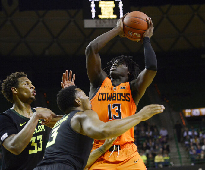Oklahoma State guard Isaac Likekele, right, looks to the basket past Baylor guard King McClure and forward Freddie Gillespie, left, during the second half of an NCAA college basketball game Wednesday, March 6, 2019, in Waco, Texas. (Ernesto Garcia/Waco Tribune Herald via AP)