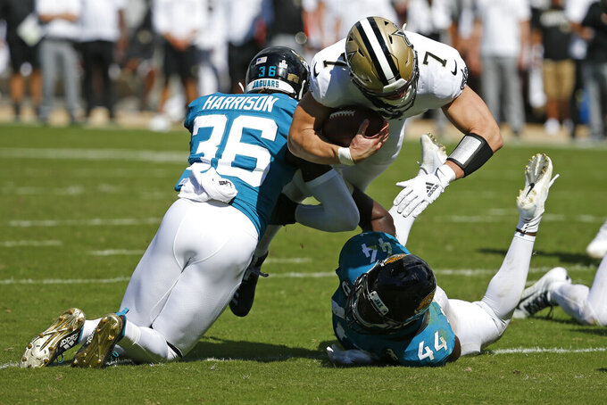 New Orleans Saints quarterback Taysom Hill (7) dives for yardage over Jacksonville Jaguars defensive back Ronnie Harrison (36) and middle linebacker Myles Jack (44) during the second half of an NFL football game, Sunday, Oct. 13, 2019, in Jacksonville, Fla. (AP Photo/Stephen B. Morton)