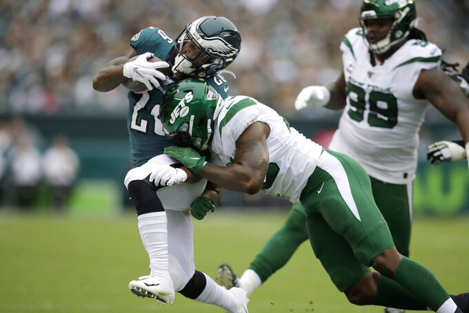 Philadelphia Eagles' Miles Sanders, left, is hit by New York Jets' Neville Hewitt during the first half of an NFL football game, Sunday, Oct. 6, 2019, in Philadelphia. (AP Photo/Matt Rourke)