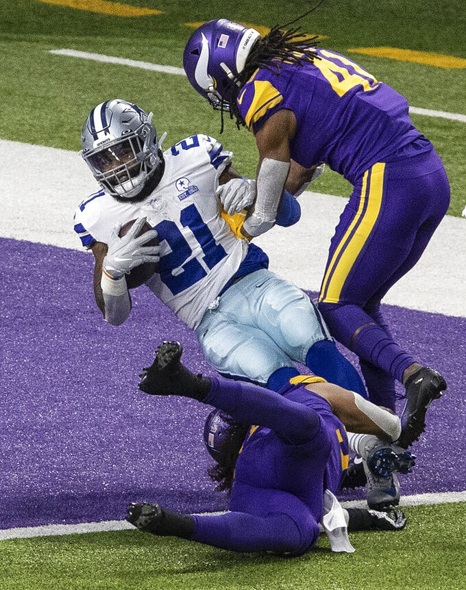 Dallas Cowboys running back Ezekiel Elliott (21) scores on a 7-yard catch over Minnesota Vikings free safety Anthony Harris (41) in the first quarter of an NFL football game in Minneapolis, Sunday, Nov. 22, 2020. ( Jerry Holt/Star Tribune via AP)
