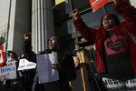 Dominique Walker, left, and Sharena Thomas, both from the group Moms 4 Housing, cheer during a rally outside of City Hall in Oakland, Calif., Tuesday, Jan. 7, 2020. Some California lawmakers said they support a group of homeless women who have been illegally living in a vacant three-bedroom house since November, partly to protest real estate speculators who drive up housing costs in the pricey San Francisco Bay Area. (AP Photo/Jeff Chiu)