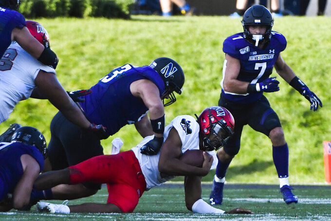 Northwestern defensive lineman Joe Spivak, left, sacks UNLV quarterback Armani Rogers, on ground, as defensive back Travis Whillock (7) looks on during the second half of an NCAA college football game, Saturday, Sept. 14, 2019, in Evanston, Ill. (AP Photo/Matt Marton)