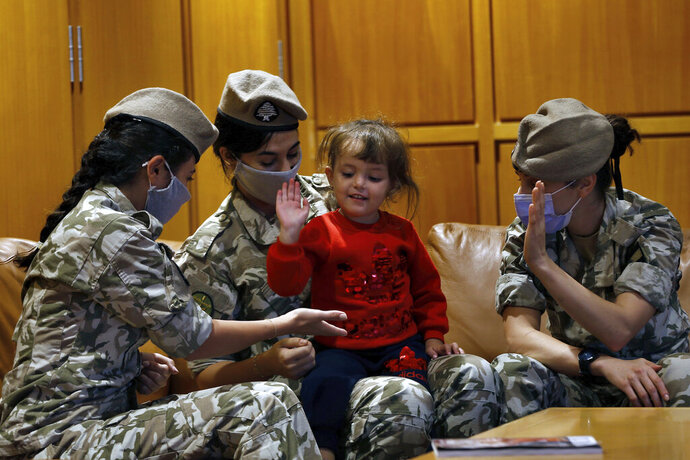 Members of the Lebanese General Security forces play with an Albanian child during an operation to take them back home to Albania from al-Hol, northern Syria, at the Rafik Hariri International Airport in Beirut, Lebanon, Tuesday, Oct. 27, 2020. The repatriation of four children and a woman related to Albanian nationals who joined Islamic extremist groups in Syria