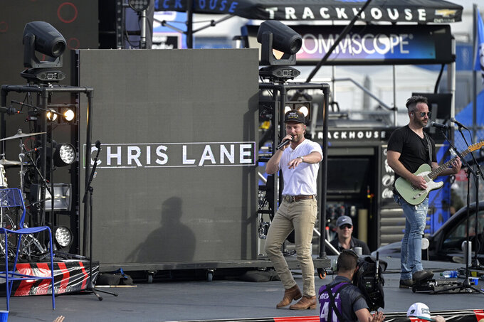 Entertainer Chris Lane, left, performs before a NASCAR Cup Series auto race at Daytona International Speedway, Saturday, Aug. 28, 2021, in Daytona Beach, Fla. (AP Photo/Phelan M. Ebenhack)