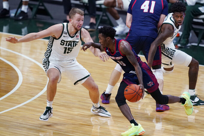 FILE- In a Dec. 4, 2020 file photo, Detroit Mercy guard Antoine Davis drives as Michigan State forward Thomas Kithier (15) defends during the first half of an NCAA college basketball game against Michigan State, in East Lansing, Mich. In a college basketball season unlike any other, players have had to adjust to coronavirus protocols and just general anxiety about what's to come. Even for those who manage to avoid catching the virus, the mental strain can be a real issue. Detroit Mercy's men's basketball program paused activities earlier this season, citing the mental health of its players. (AP Photo/Carlos Osorio, File)