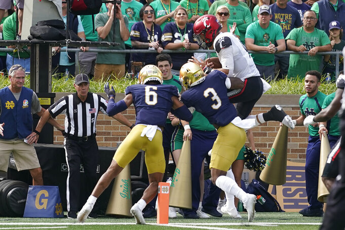 Cincinnati quarterback Desmond Ridder (9) tries to leap over Notre Dame's Clarence Lewis (6) and Houston Griffith (3) during the first half of an NCAA college football game, Saturday, Oct. 2, 2021, in South Bend, Ind. (AP Photo/Darron Cummings)