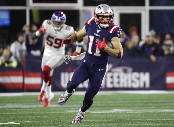 New England Patriots wide receiver Julian Edelman runs from New York Giants linebacker Lorenzo Carter, rear, after catching a pass in the first half of an NFL football game, Thursday, Oct. 10, 2019, in Foxborough, Mass. (AP Photo/Elise Amendola)