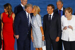 French President Emmanuel Macron, second right, and German Chancellor Angela Merkel watch Brigitte Macron kissing U.S President Donald Trump while first lady Melania Trump, left, looks away, during the G7 family photo Sunday, Aug. 25, 2019 in Biarritz. A top Iranian official paid an unannounced visit Sunday to the G-7 summit and headed straight to the buildings where leaders of the world's major democracies have been debating how to handle the country's nuclear ambitions. (AP Photo/Francois Mori)