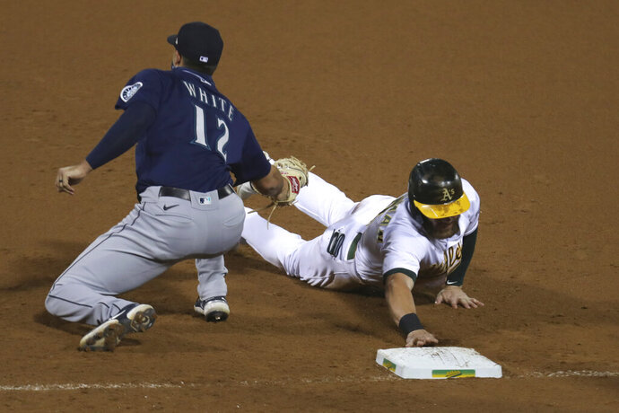 Oakland Athletics' Robbie Grossman, right, is tagged out at first base by Seattle Mariners' Evan White during the seventh inning of a baseball game in Oakland, Calif., Friday, Sept. 25, 2020. (AP Photo/Jed Jacobsohn)