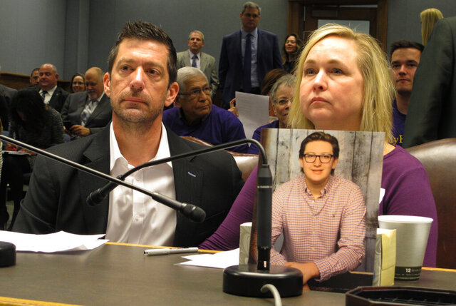 FILE - In this Wednesday, March 21, 2018, file photo, Stephen and Rae Ann Gruver sit in a House committee room behind a photo of their son, 18-year-old Maxwell Gruver, a Louisiana State University freshman who died with a blood-alcohol content six times higher than the legal limit for driving in what authorities say was a hazing incident, in Baton Rouge, La. A federal appeals court says Stephen and Rae Ann Gruver can pursue a lawsuit that says the university disciplines sororities and fraternities differently because of gender. (AP Photo/Melinda Deslatte, File)
