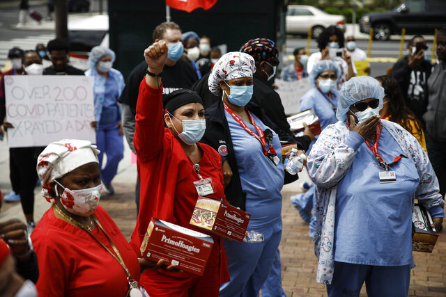 Medical professionals and their supporters wearing protective face masks as a precaution against the coronavirus demand safer working conditions and policies during a May Day protest near Temple University Hospital in Philadelphia, Friday, May 1, 2020. (AP Photo/Matt Rourke)