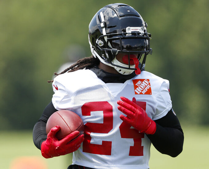 "FILE - In this Tuesday, June 11, 2019, file photo, Atlanta Falcons running back Devonta Freeman (24) runs during an NFL football practice in Flowery Branch, Ga.  When Atlanta Falcons coach Dan Quinn calls running back Devonta Freeman a ""multiplier"" he is talking about Freeman making every other player on the offense better. That makes Freeman's health an obvious key after he was limited by injuries to two games in 2018. (AP Photo/John Bazemore, File)"
