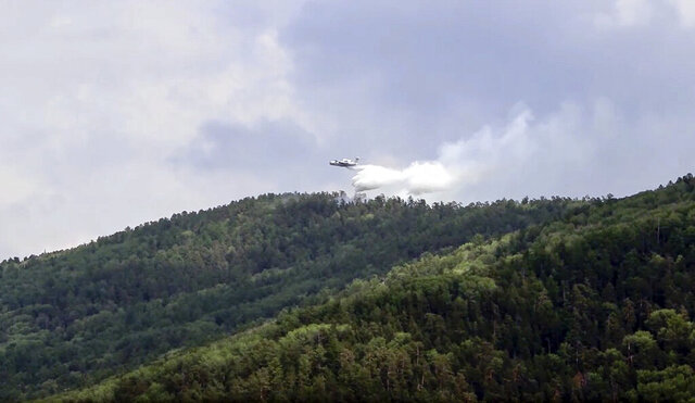 """FILE - In this Friday, July 10, 2020 file image taken from video provided by Russian Emergency Ministry, a Russian Emergency Ministry's Beriev plane BE-200 Be-200 multipurpose amphibious aircraft releases water in the Trans-Baikal National Park in Buryatia, southern Siberia, Russia. The United Nations weather agency said Tuesday Sept. 1, 2020, this summer will go down for leaving a """"deep wound"""" in the cryosphere -- the planet's frozen parts -- amid a heat wave in the Arctic, shrinking sea ice and the collapse of a leading Canadian ice shelf. (Russian Emergency Ministry Press Service via AP, File)"""
