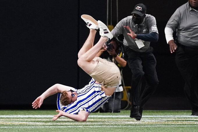A fan who ran onto the field during an NCAA college football game between Georgia Tech and North Carolina is detained by security officers Saturday, Sept. 25, 2021, in Atlanta. (AP Photo/John Bazemore)