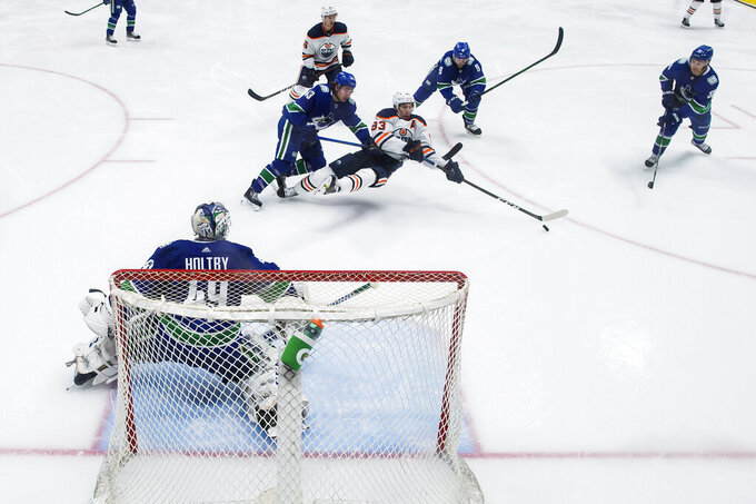 Vancouver Canucks' Quinn Hughes (43) hooks Edmonton Oilers' Ryan Nugent-Hopkins (93) to the ice in front of Vancouver goalie Braden Holtby (49) during the second period of an NHL hockey game, Monday, May 3, 2021, in Vancouver, British Columbia. (Darryl Dyck/The Canadian Press via AP)