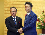 Okinawa Governor Denny Tamaki, left, and Japanese Prime Minister Shinzo Abe shake hands during a meeting at Abe's office in Tokyo Friday, Oct. 12, 2018. Tamaki won the election for governor at the end of last month, becoming the first Amerasian to lead the southwestern Japanese islands. (AP Photo/Eugene Hoshiko, Pool)