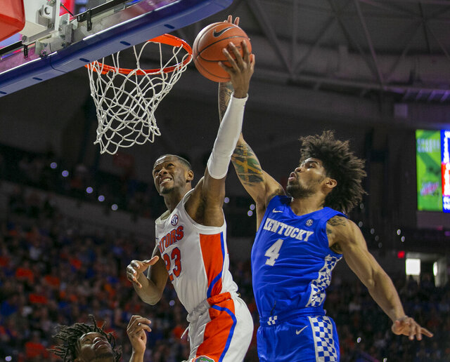 Florida guard Scottie Lewis (23) shots against Kentucky forward Nick Richards (4) during the first half of an NCAA college basketball game Saturday, March 7, 2020, in Gainesville, Fla. (AP Photo/Alan Youngblood)