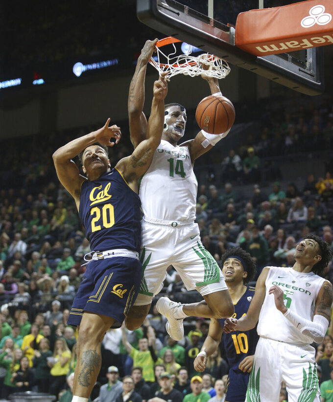 Oregon's Kenny Wooten, center, dunks over California's Matt Bradley, left, and Justice Sueing, center right, and Oregon's Miles Norris, right, during the first half of an NCAA college basketball game Wednesday, Feb. 6, 2019, in Eugene, Ore. (AP Photo/Chris Pietsch)