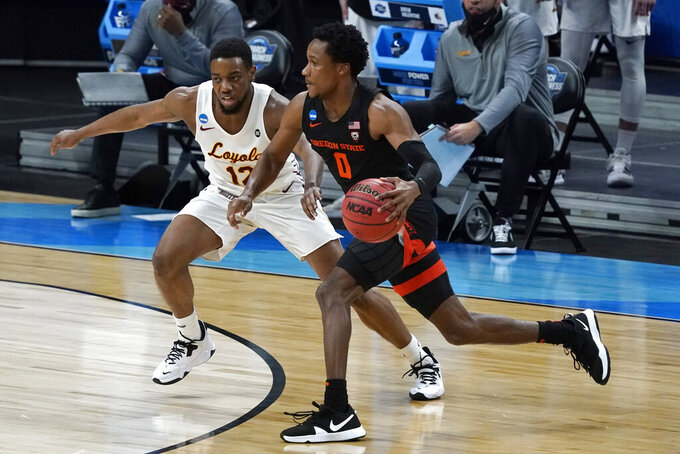 Oregon State guard Gianni Hunt (0) drives past Loyola Chicago guard Marquise Kennedy (12) during the first half of a Sweet 16 game in the NCAA men's college basketball tournament at Bankers Life Fieldhouse, Saturday, March 27, 2021, in Indianapolis. (AP Photo/Jeff Roberson)
