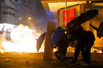 Protesters cover with umbrellas from tear gas canister in the Kowloon area of Hong Kong, Monday, Nov. 18, 2019. As night fell in Hong Kong, police tightened a siege Monday at a university campus as hundreds of anti-government protesters trapped inside sought to escape. (AP Photo/Vincent Yu)