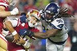 FILE - In this Nov. 11, 2019, file photo, San Francisco 49ers quarterback Jimmy Garoppolo, left, avoids being sacked by Seattle Seahawks defensive end Jadeveon Clowney (90) during the second half of an NFL football game in Santa Clara, Calif.  Even with the status of the upcoming season uncertain because of the coronavirus pandemic, teams continue to tinker with their rosters by adding players they hope will help them win — whenever, or if, they actually play. Many believed Clowney would be snatched up by a team desperate for a pass-rushing presence during the first few days of free agency. And, for big-time bucks. Instead, the 2014 No. 1 overall pick is still unsigned two months later and potentially looking at a one-year, prove-it deal. A return to Seattle isn't out of the question. (AP Photo/Tony Avelar, File)