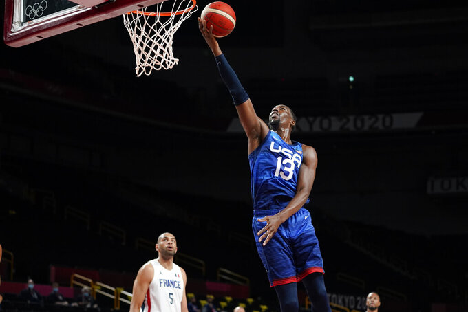 United States' Bam Adebayo (13) drives to the basket ahead of France's Nicolas Batum, left, during a men's basketball preliminary round game at the 2020 Summer Olympics, Sunday, July 25, 2021, in Saitama, Japan. (AP Photo/Charlie Neibergall)