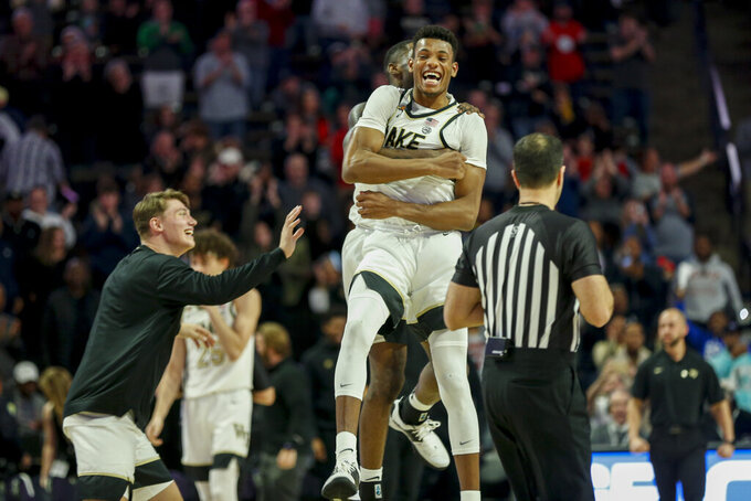 Wake Forest forward Ody Oguama, center, celebrates with teammates as Wake Forest defeats Xavier in an NCAA college basketball game in Winston-Salem, N.C., Saturday, Dec. 14, 2019. (AP Photo/Nell Redmond)