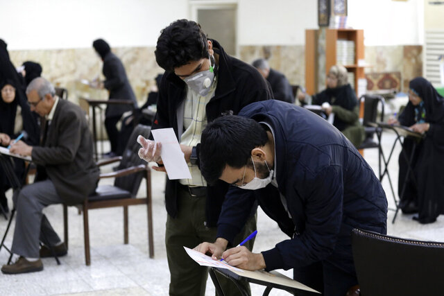 Voters with face masks fill out their ballots in the parliamentary elections at a polling station in Tehran, Iran, Friday, Feb. 21, 2020. Iranians began voting for a new parliament Friday, with turnout seen as a key measure of support for Iran's leadership as sanctions weigh on the economy and isolate the country diplomatically. Also looming over the election is the threat of the new coronavirus, which has been confirmed in five people in Iran this week, including two elderly citizens who died in the city of Qom. Concerns over the spread of the virus, which originated in central China, prompted authorities in Iran to close all schools and Shiite seminaries in Qom. (AP Photo/Vahid Salemi)