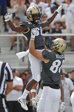 Central Florida running back Greg McCrae, left, celebrates his touchdown run against Stanford as he gets a lift from teammate tight end Jake Hescock, right, during the first half of an NCAA college football game, Saturday, Sept. 14, 2019, in Orlando, Fla. (AP Photo/John Raoux)
