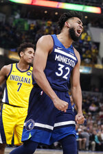 Minnesota Timberwolves center Karl-Anthony Towns (32) reacts after being fouled during the first half of the team's NBA basketball game against the Indiana Pacers in Indianapolis, Friday, Jan. 17, 2020. (AP Photo/Michael Conroy)