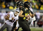 Oregon's Justin Herbert, right, scrambles away from Washington State's Ron Stone Jr. during the first quarter of an NCAA college football game, Saturday, Oct. 26, 2019, in Eugene, Ore. (AP Photo/Chris Pietsch)