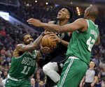 Boston Celtics' Kyrie Irving (11) forces a jump ball against Milwaukee Bucks' Giannis Antetokounmpo, center, during the first half of an NBA basketball game Thursday, Feb. 21, 2019, in Milwaukee. (AP Photo/Aaron Gash)