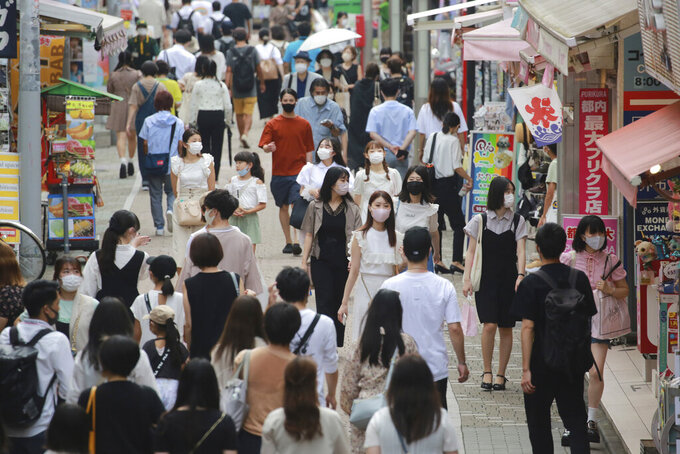 People wearing face masks to protect against the spread of the coronavirus walk through Takeshita street in Tokyo, Wednesday, July 28, 2021. Tokyo Gov. Yuriko Koike on Wednesday urged younger people to cooperate with measures to bring down the high number of infections and get vaccinated, saying their activities are key to slowing the surge during the Olympics.  (AP Photo/Koji Sasahara)