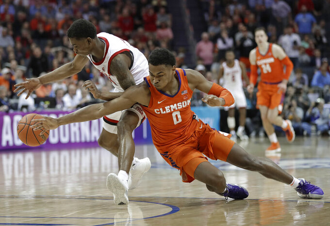 Clemson's Clyde Trapp (0) and North Carolina State's Markell Johnson chase a loose ball during the second half of an NCAA college basketball game in the Atlantic Coast Conference tournament in Charlotte, N.C., Wednesday, March 13, 2019. (AP Photo/Nell Redmond)