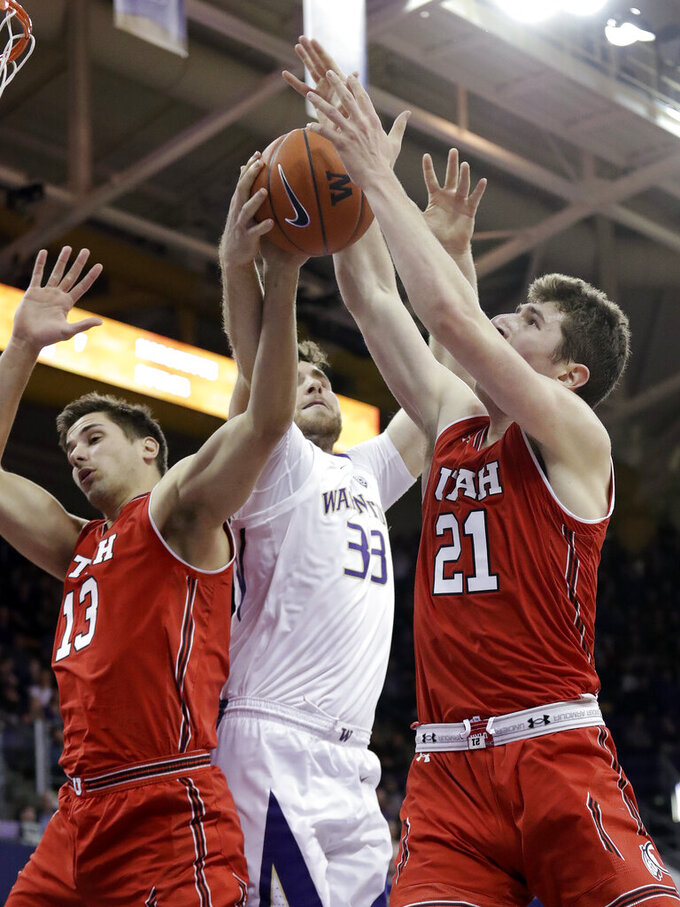 Washington's Sam Timmins (33) and Utah's Novak Topalovic (13) and Riley Battin (21) vie for a rebound during the first half of an NCAA college basketball game Wednesday, Feb. 20, 2019, in Seattle. (AP Photo/Elaine Thompson)