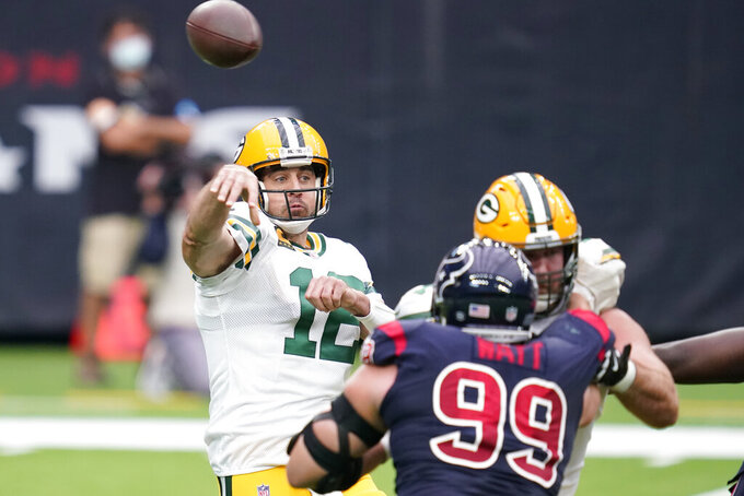 Green Bay Packers quarterback Aaron Rodgers, left, throws over Houston Texans defensive end J.J. Watt (99) during the first half of an NFL football game Sunday, Oct. 25, 2020, in Houston. (AP Photo/Sam Craft)