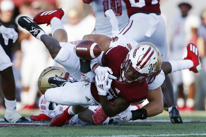 Massachusetts wide receiver Eric Collins (80) fumbles the ball during the second half of an NCAA college football game against Boston College, Saturday, Sept. 11, 2021, in Amherst, Mass. The ball was recovered by Boston College defensive back Jaiden Woodbey and returned for a touchdown. (AP Photo/Michael Dwyer)