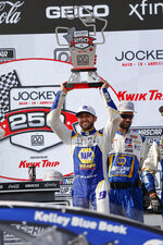 Chase Elliott (9) holds up his trophy after winning a NASCAR Cup Series auto race Sunday, July 4, 2021, at Road America in Elkhart Lake, Wis. (AP Photo/Jeffrey Phelps)