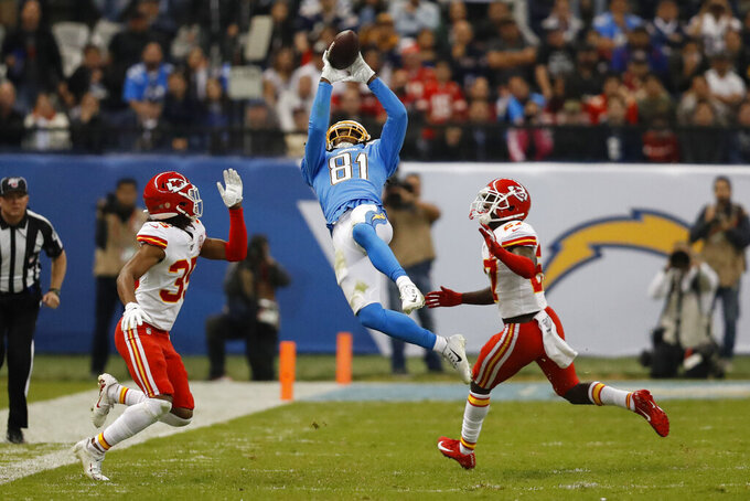 Los Angeles Chargers wide receiver Mike Williams, center, makes a catch as Kansas City Chiefs cornerback Charvarius Ward, left, and defensive back Rashad Fenton, right, defend, during the second half of an NFL football game Monday, Nov. 18, 2019, in Mexico City. (AP Photo/Eduardo Verdugo)