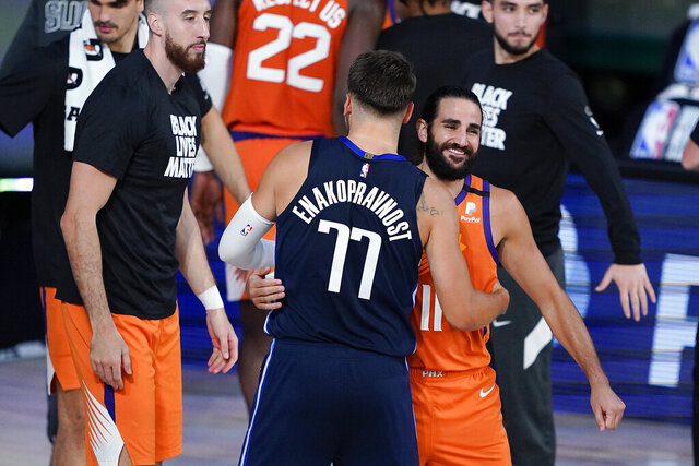 Dallas Mavericks guard Luka Doncic (77) embraces Phoenix Suns guard Ricky Rubio (11) after playing in an NBA basketball game Sunday, Aug. 2, 2020, in Lake Buena Vista, Fla. Phoenix won 117-115. (AP Photo/Ashley Landis, Pool)