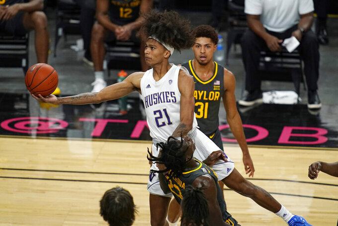 Washington's RaeQuan Battle (21) fouls Baylor's Jonathan Tchamwa Tchatchoua (23) during the first half of an NCAA college basketball game Sunday, Nov. 29, 2020, in Las Vegas. (AP Photo/John Locher)