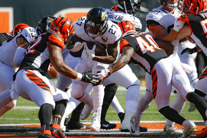 Jacksonville Jaguars running back Leonard Fournette (27) runs the ball against Cincinnati Bengals defensive back Brandon Wilson (40) in the first half of an NFL football game, Sunday, Oct. 20, 2019, in Cincinnati. (AP Photo/Frank Victores)