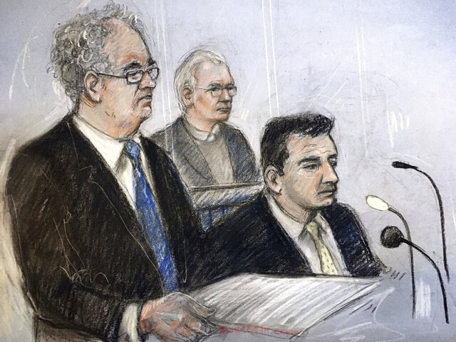 Court artist sketch by Elizabeth Cook, depicting Julian Assange, centre, in the dock with his defence team, Edward Fitzgerald QC, left, and Mark Simmons QC, at Belmarsh Magistrates' Court in London, during an extradition hearing, Monday Feb. 24, 2020.  The U.S. government began outlining its extradition case against Wikileaks founder Julian Assange in a London court. (Elizabeth Cook/PA via AP)
