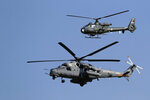 A Russian army helicopter MI-35, front, performs with a Serbian army Gazelle helicopter during a military parade at the military airport Batajnica, near Belgrade, Serbia, Saturday, Oct. 19, 2019. Medvedev arrived on a one-day official visit to Serbia during which he attend military parade commemorating the 75th anniversary of the liberation of the Serbian capital from the Nazi German occupation by the Red Army and Communist Yugoslav Partisans. (AP Photo/Darko Vojinovic)