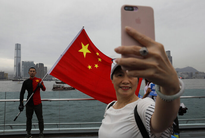 In this Saturday, Aug. 17, 2019 file photo, pro-China supporters take a selfie with a Chinese national flag to support police and anti-violence during a rally at a park in Hong Kong. Twitter said Monday it has suspended more than 200,000 accounts that it believes were part of a Chinese government influence campaign targeting the protest movement in Hong Kong. (AP Photo/Vincent Yu)