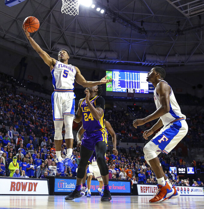 Florida guard KeVaughn Allen (5) gathers in an offensive rebound in front of LSU forward Emmitt Williams (24) during the first half of an NCAA college basketball game in Gainesville, Fla., Wednesday, March 6, 2019. (AP Photo/Gary McCullough)