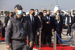 Israeli Prime minister Benjamin Netanyahu, center, walks during an immigration ceremony at the Ben Gurion airport near Tel Aviv, Israel, Thursday, Dec. 3, 2020. Hundreds of Ethiopian immigrants on Thursday arrived to a festive ceremony at Israel's international airport, as the government took a step toward carrying out its pledge to reunite hundreds of families split between the two countries. (AP Photo/Sebastian Scheiner)